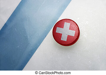 old hockey puck with the national flag of switzerland. -...