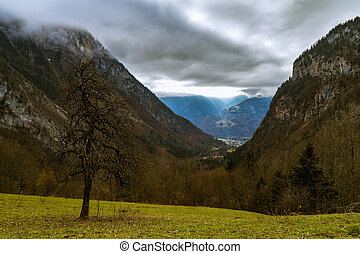 Autumn valley in the alps with sunlight breaking through the...