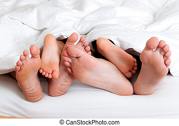 Soles of a family in bed under the ceiling - The soles of a...