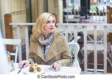 Close up happy adult blond woman in outdoors cafe looking...