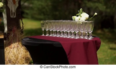 Buffet table with empty champagne glasses. Standing in the...