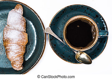 Fresh croissant with a hot cup of coffee