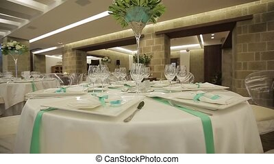 Served tables with wine glasses, white tablecloth and wooden...