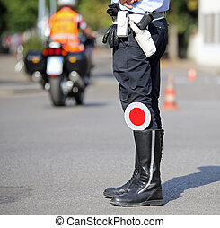 traffic pallet in the black boots of a traffic warden in the...