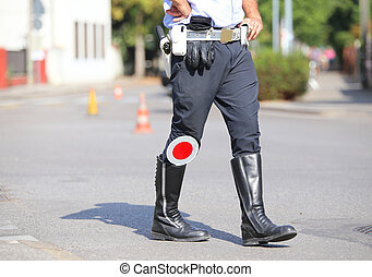 black boots and traffic pallet of a traffic policeman in the...