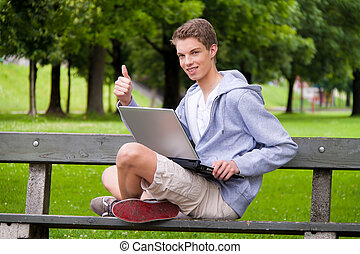 Young man with laptop in the park - A young man with laptop...