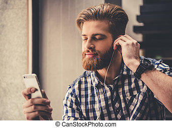 Handsome young man in earphones is enjoying the music with...