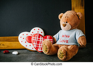 Beautiful background for Valentine's day with Teddy bear and gingerbread hearts. Free space for your text