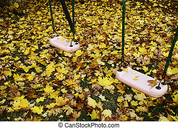 seesaw on the playground covered with autumn leaves - teeter...
