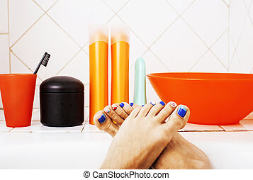 woman legs in bathroom with lot of stylish stuff for care, pedicure blue nails