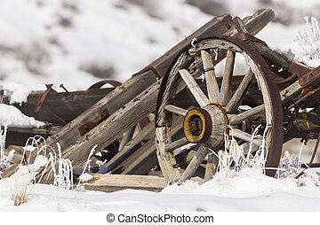 Old broken wagon with wheel in snow and frost with winter...