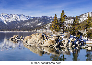 Winter shot of Lake Tahoe with snow on rocks and mountains....
