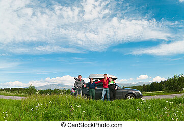 Traveling by car - A family of four standing on a road near...