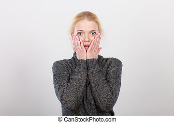 Shocked woman holding hands on face