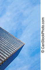 Partial view of a corporate skyscraper from the bottom in front of cloudy sky