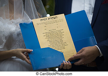 Jewish wedding, a contract, close-up - wedding rings and...