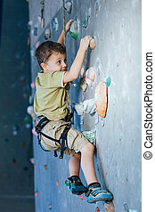 little boy climbing a rock wall indoor. Concept of sport...