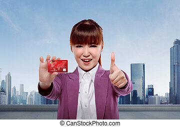 Young asian business woman showing credit card