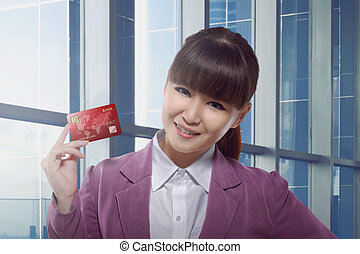 Beautiful asian business woman holding credit card in the...