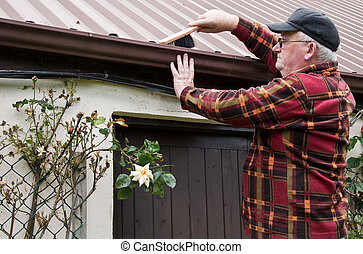 senior male cleaning out gutter outside house - photo senior...