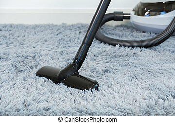 cleaning carpet floor with vacuum cleaner in the living room