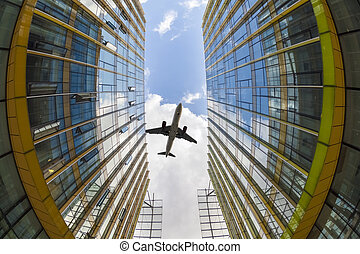 modern glass buildings and airplane - airplane flew above...