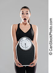 Shocked astonished young woman athlete holding weighing scale