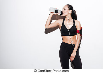 Attractive woman with armband drinking water and listening to music