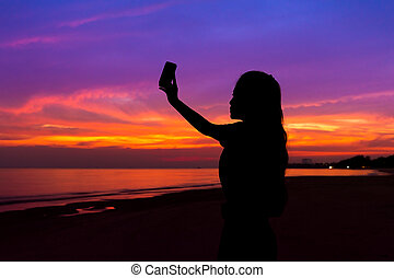 Silhouette of woman taking photo of sunset with mobile phone, at sea beach