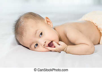 portrait of baby on a bed in bedroom