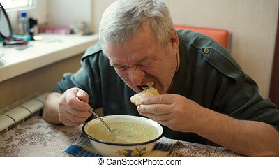Rural Man eating soup - Rustic aged man eating a soup with...