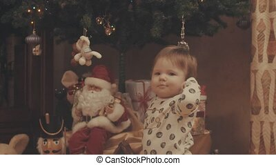 Little baby playing with Santa Claus. Eye level shot,