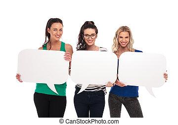 three happy casual women holding blank speech bubbles boards...