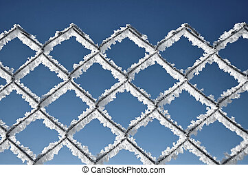 Metallic net covered with hoarfrost. Extreme cold weather concept