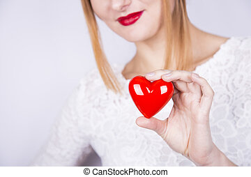 Smiling beautiful red-haired woman holding red heart on white background