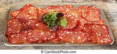 Platte mit Salami und Salat belegt