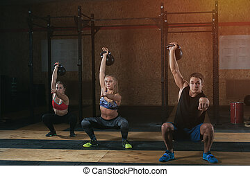 Three adults doing squats with kettle bells - Three muscular...