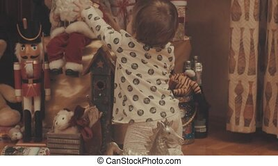 Little baby pulling the hairs from Santa Claus's beard. Eye...