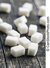 White sugar cubes. - White sugar cubes on old wooden table.