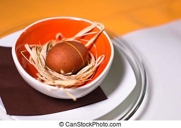 Easter egg on the straw in colored plate and tablecloth -...