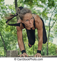 Female athlete jumping across wooden hurdle