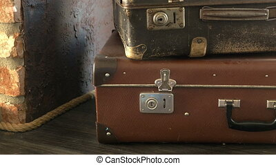 Two old suitcases are on the shelf. Camera movement.