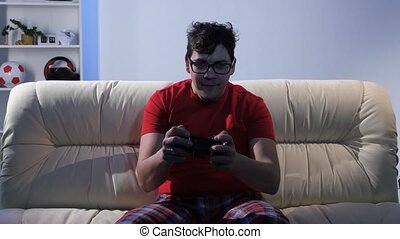 Bespectacled man playing video game while sitting on the...
