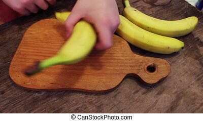Slicing a banana into thin slices - The boy cut the banana...
