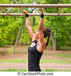 Monkey bars workout - Female athlete crossing monkey bars