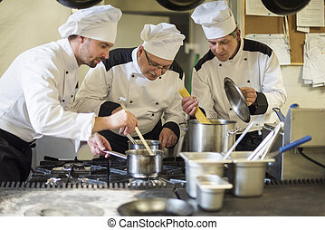 Three men busy in the commercial kitchen