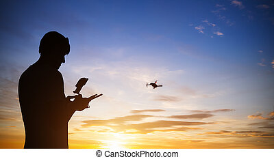 Drone pilot with quadrocopter. Silhouette against the sunset...