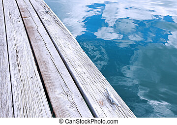 Fiji - Wooden jetty pier and reflection of sky in blue...