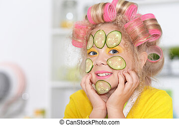 cute little girl making facial mask with cucumber