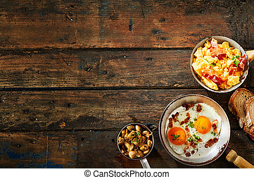 Pot of scrambled eggs and bacon on rustic table beside...